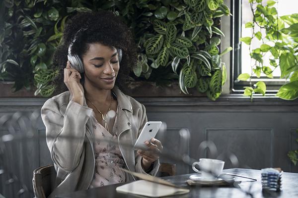 Woman with smartphone wearing QC35II headphones