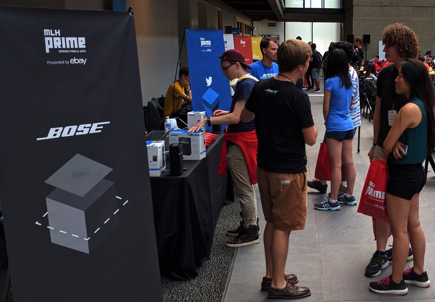 A crowd of people at a Bose hackathon booth.
